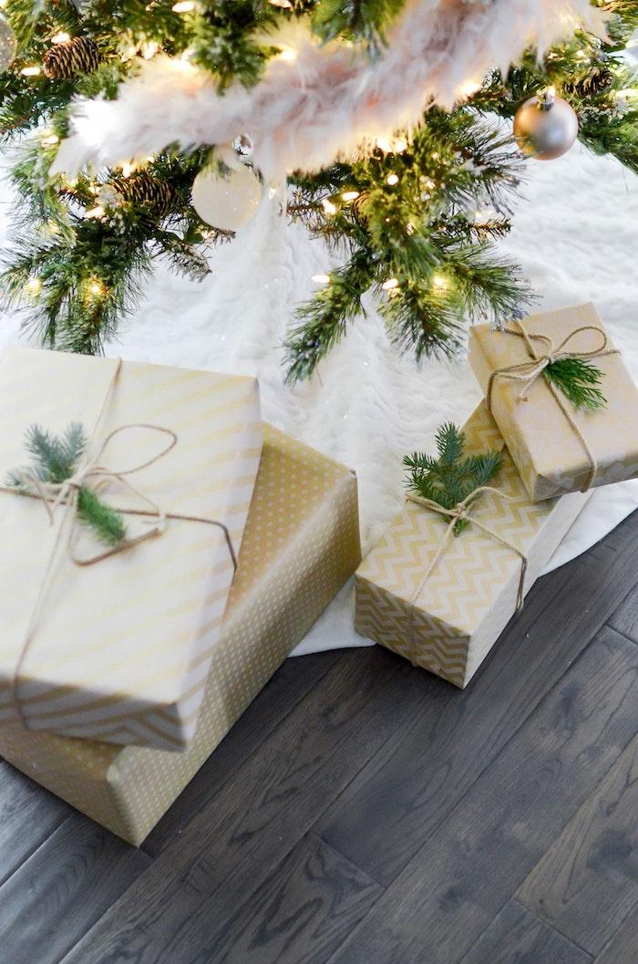Parfum à offrir en cadeau pour femme ou pour homme, cadeaux joliment emballés sous l'arbre de noël décoré