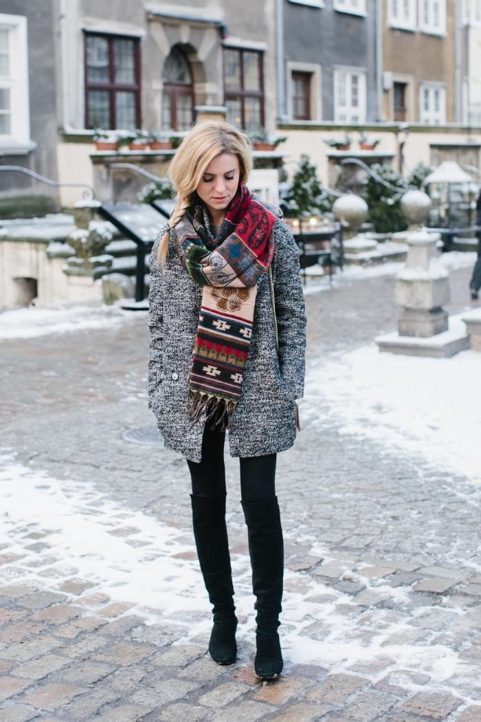 vetement femme tendance cozy, modèle de manteau loose en gris clair porté avec pantalon fit noir et écharpe multicolore