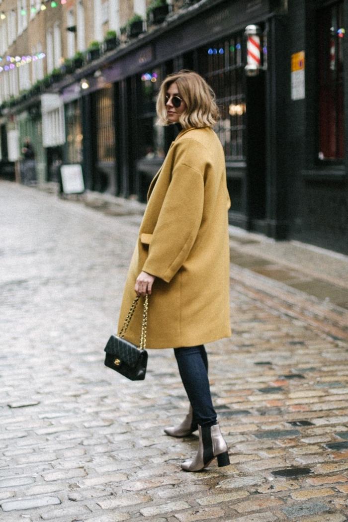 modèle de manteau femme hiver 2020 de couleur jaune à taille oversize avec poche, look femme chic en jeans et chaussures hautes