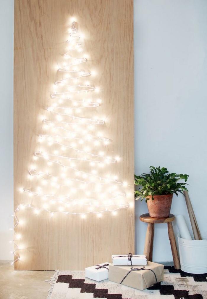 modèle de panneau lumineux pour Noël fait main avec planche de bois troués et guirlande lumineuse en forme de sapin