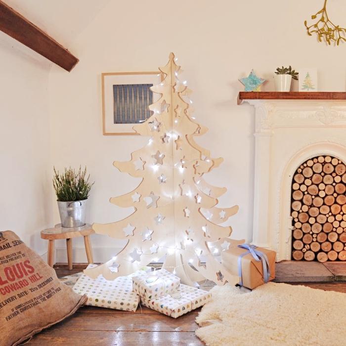 diy decoration noel a faire soi meme, modèle d'arbre de Noël fait en bois clair et décoré avec guirlande lumineuse