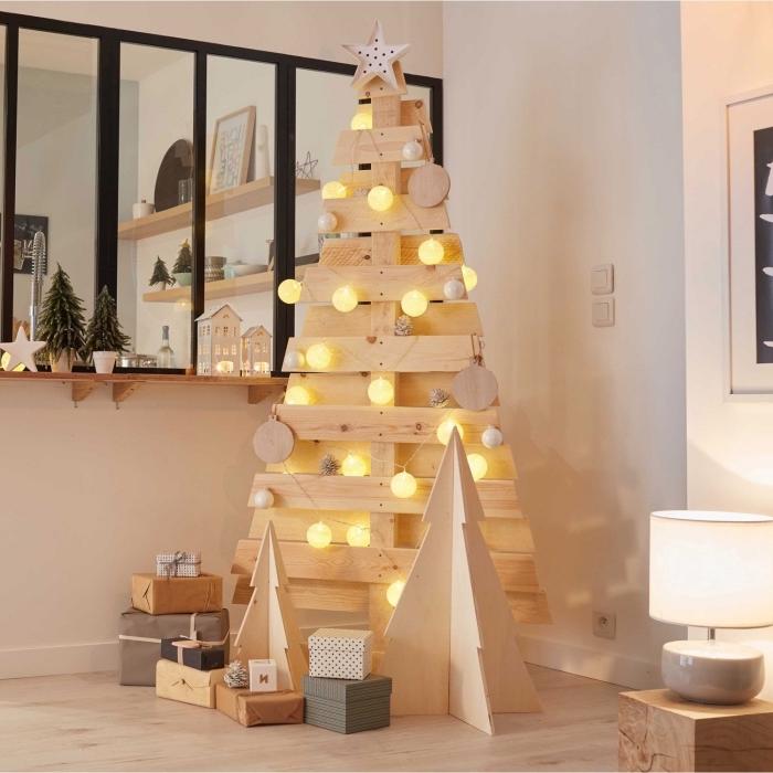 idée fabrication de sapin en palette ou planches de bois, modèle de sapin fait maison de style minimaliste décoré avec guirlande lumineuse boules
