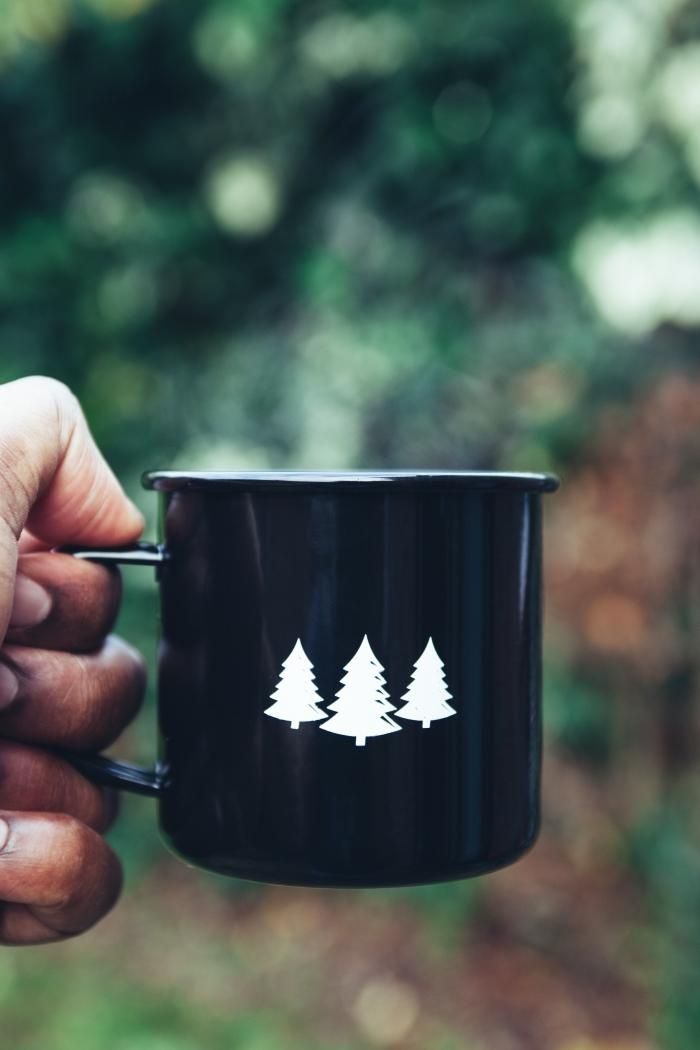 wallpaper iphone Noel de style minimaliste, photo verrouillage d'écran sur le thème camping Noël avec un mug noir à motifs mini sapins blancs