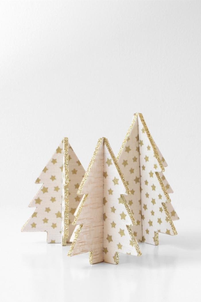 exemple de décoration de noel à fabriquer en bois, modèles de mini sapins fabriqués en morceaux de bois décorés avec papier scrapbooking
