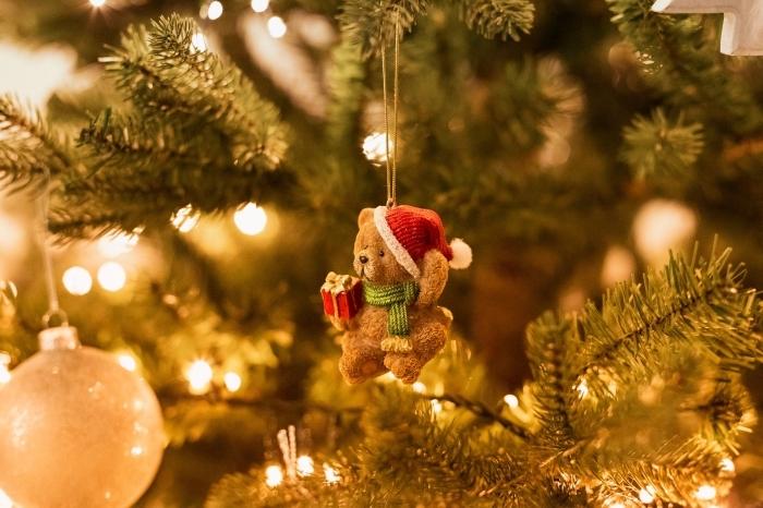 photo sapin de noel naturel décoré avec guirlande lumineuse et figurine ours de Noel, idée fond d'écran ordinateur pour Noel