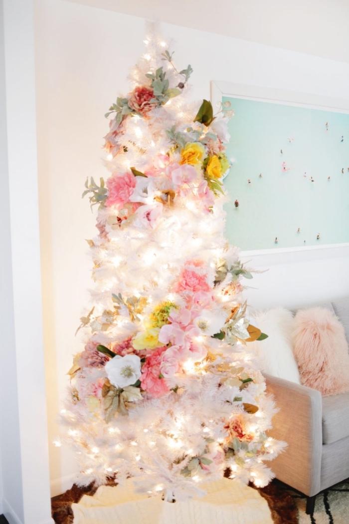 modèle de sapin de noel artificiel aux branches blanches décoré avec guirlande lumineuse et florale, idée comment decorer un sapin