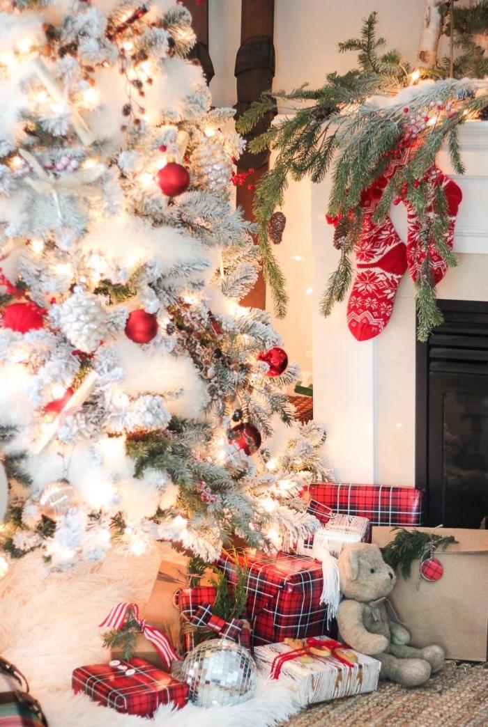 modèle de sapin rouge et blanc décoré avec figurines pommes de pin argentées et cadeaux emballés en papier motifs carreaux rouges