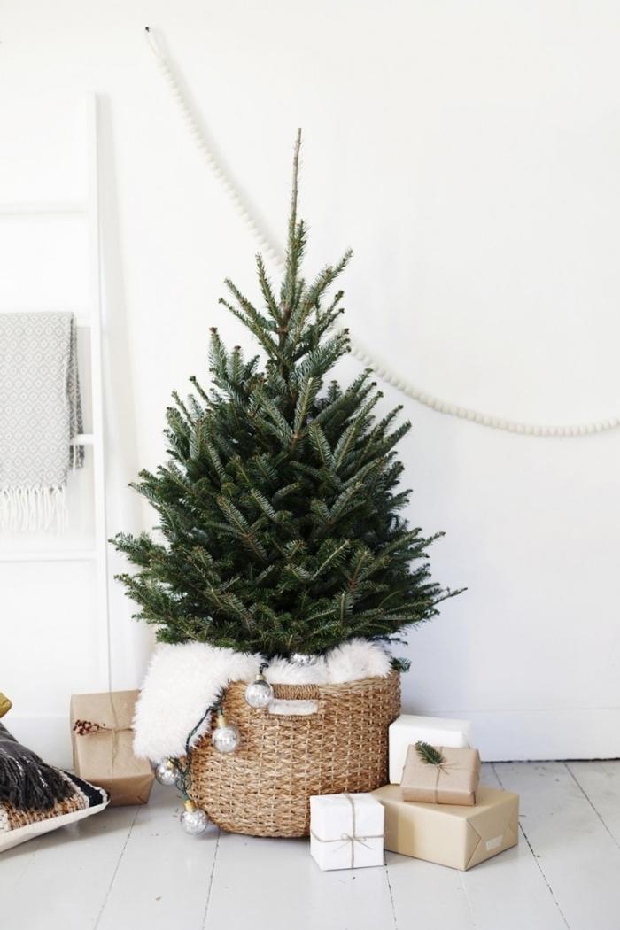 decoration sapin de noel minimaliste dans un salon blanc avec parquet bois blanc, arbre de noel dans un panier tressé avec plaid moelleux