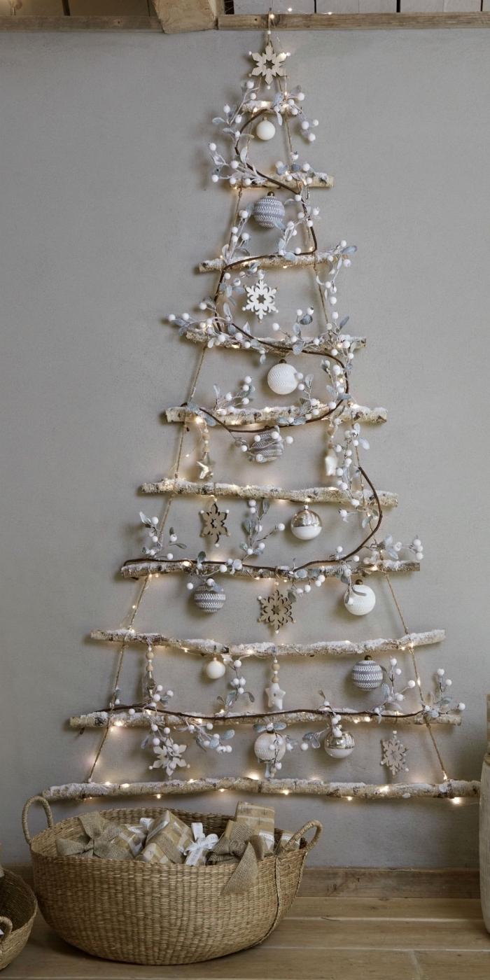 diy décoration murale pour noël fabriqué avec branches et corde en forme de sapin minimaliste décoré avec flocons de neige