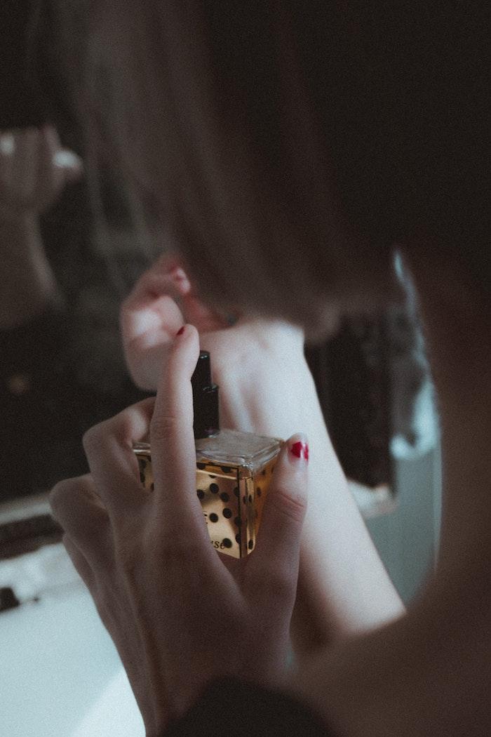 Femme avec bouteille de parfum dans la main, idée quel parfum choisir pour offrir comme cadeau