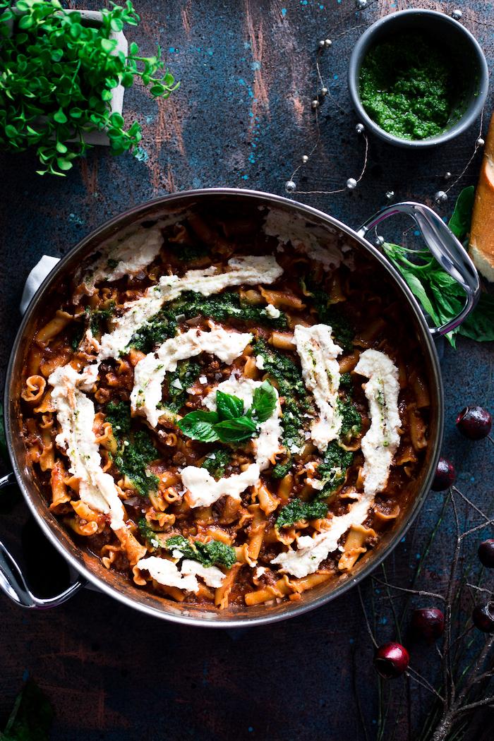 pasta ou pâtes à la sauce bolognese de tomates et viande hachée avec du pesto de basilic et sauce en top