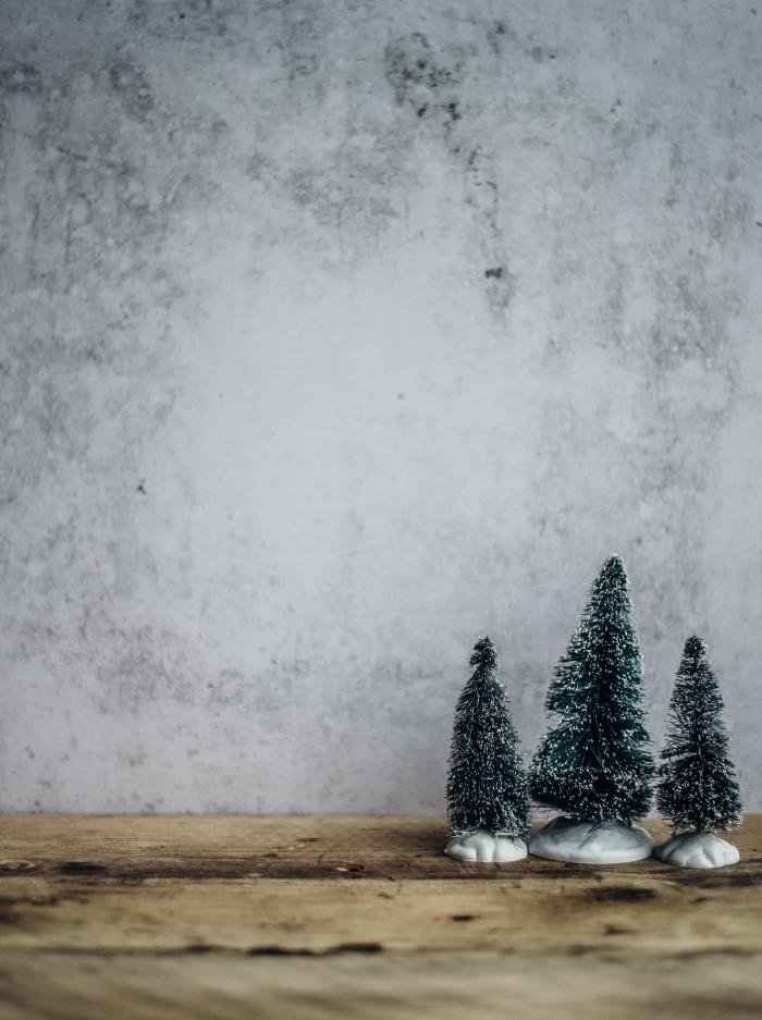 idée fond d'écran Noël minimaliste pour smartphone, photo de mini figurines d'arbres de Noël enneigés devant un mur bétonné