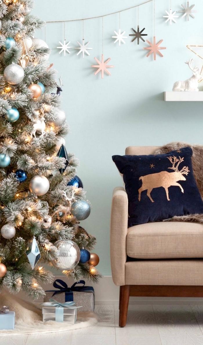 design intérieur moderne dans un salon aux murs bleu pastel aménagé avec meubles tissu et bois foncé, déco sapin de Noel avec ornements métalliques