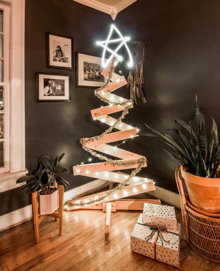 idée comment décorer une chambre noire moderne avec un sapin fait maison en planches de bois décoré de guirlandes