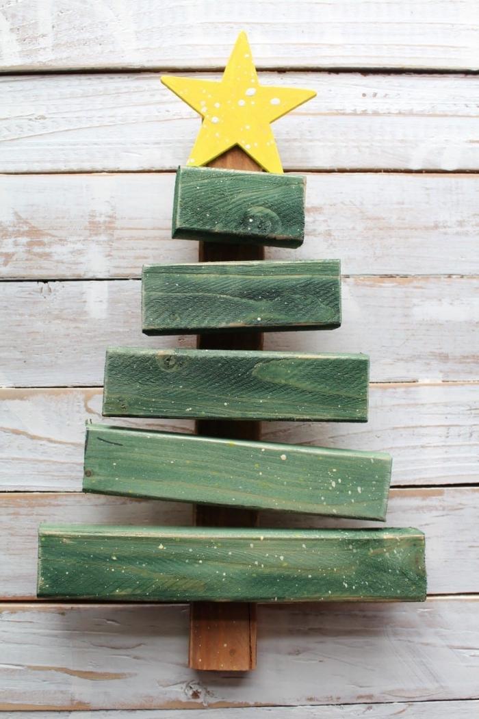 modèle de mini sapin fait main avec morceaux de bois recyclé repeint en vert et décoré avec une étoile jaune au sommet