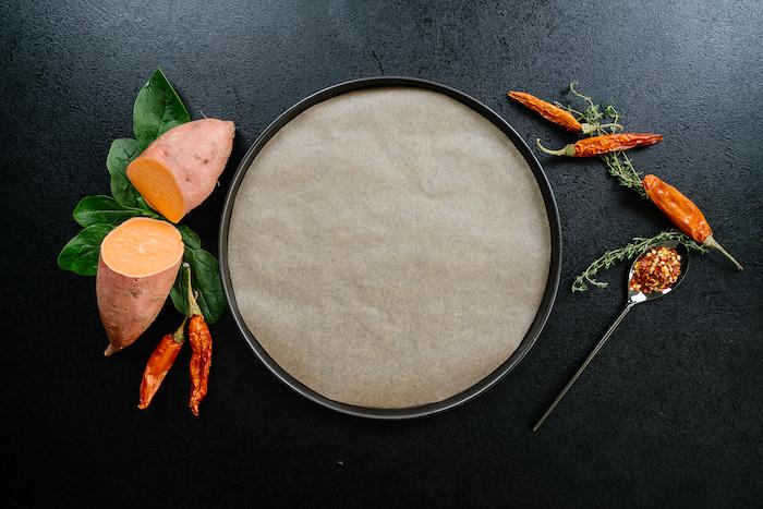 une plaque de four recouvert de papier cuisson entourée de patates douces et des piments rouges