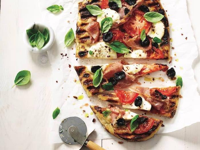recette pour faire une pizza naan aux tomates, moxarella, prosciutto et des feuilles de basilic fraîches