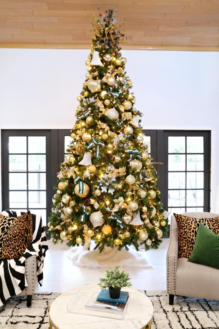 deco sapin noel stylé avec boules dorées et guirlande lumineuse, design intérieur moderne dans un salon blanc et bois