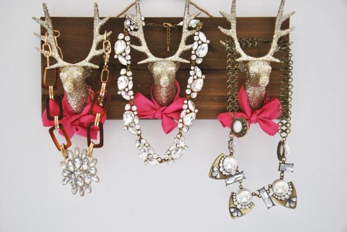 modèle de porte collier à faire soi-même, diy rangement pour colliers avec une planche bois foncé et figurine tête de cerf dorée