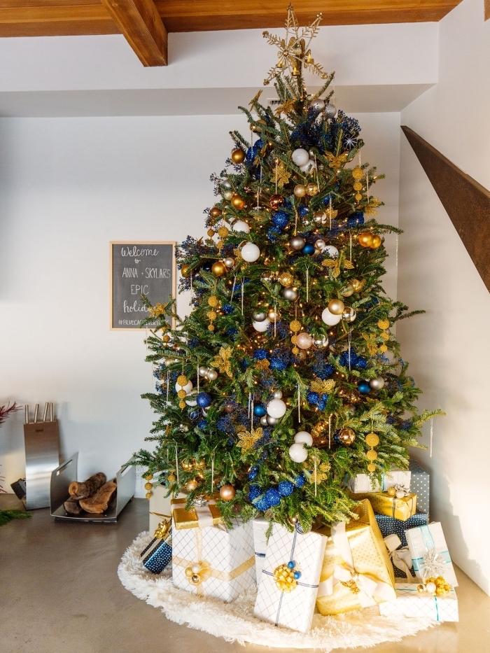 décoration de Noël dans une pièce blanche avec plafond en bois et sol ciment, exemple de sapin de noel décoré en or et bleu