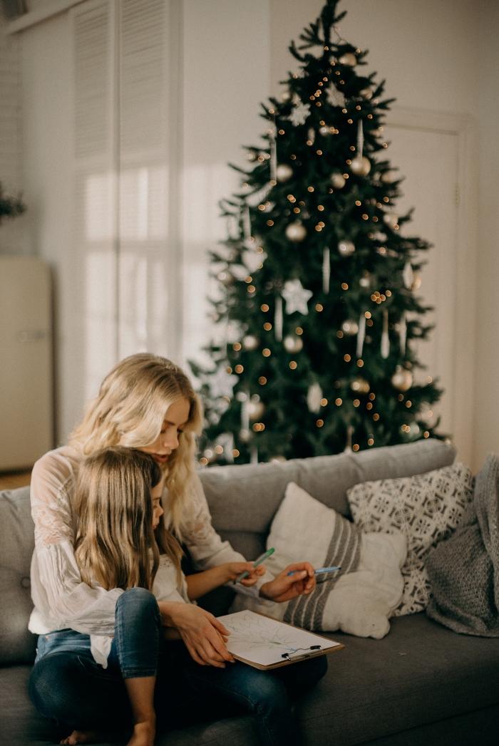 exemple de sapin de noel décoré en blanc et or, idée photo de famille pour noel, mère et fille sur un canapé gris dans un salon blanc
