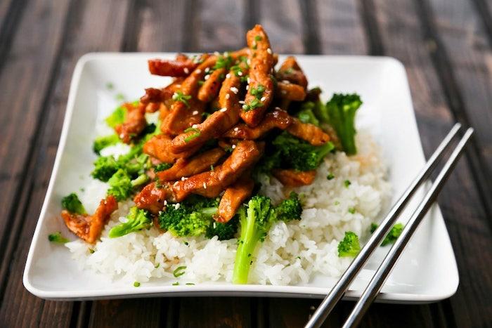 assiette carrée remplie de riz et brocolis en canapé avec bouchées de porc glacées à l ail et gingembre en top