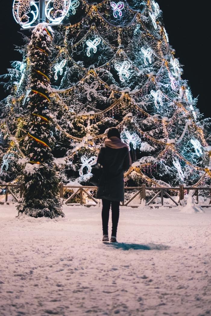 fond d'écran pour verrouillage iphone avec une fille habillée en manteau hiver et écharpe rose devant sapin de noel décoré