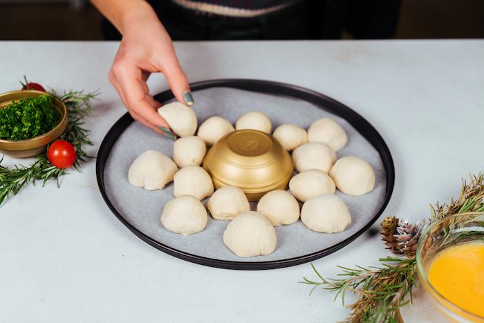 idee apero dinatoire de fete, pain constitué de boules de pâte et mozzarella à ranger sur une plaque de four