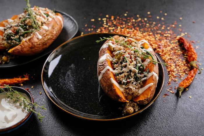 patate douce au four farcie de quinoa, pois chiches avec de la sauce tahini et du thym en top, plat healthy vegan