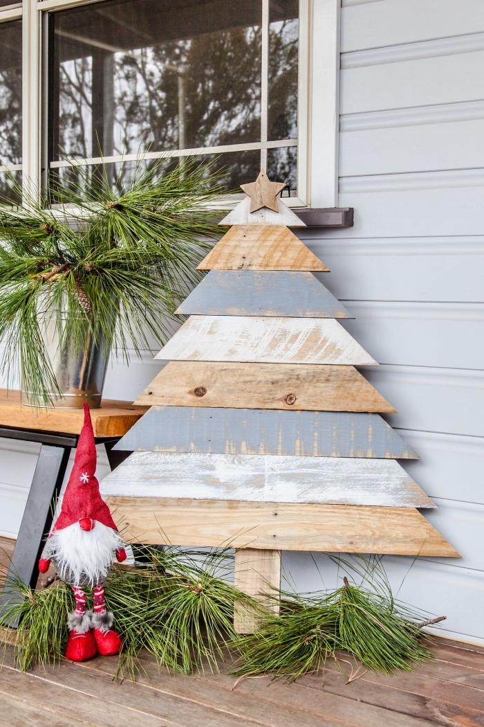 idée deco de noel en bois à fabriquer soi-même pour décorer sa véranda, modèle de sapin en planches bois peintes en blanc et gris