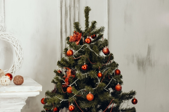 idee deco sapin de noel avec ornements rouges et guirlandes lumineuse, déco salon blanc pour Noël avec arbre de Noël artificiel