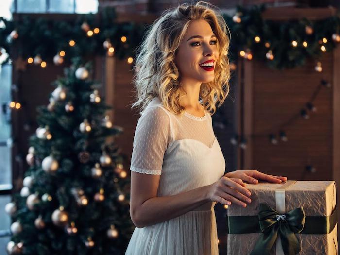 Belle femme blonde souriante, robe blanche en dentelle moulante, robe pour les fetes, tenue de soirée femme photo devant le sapin avec un cadeau joliment emballé