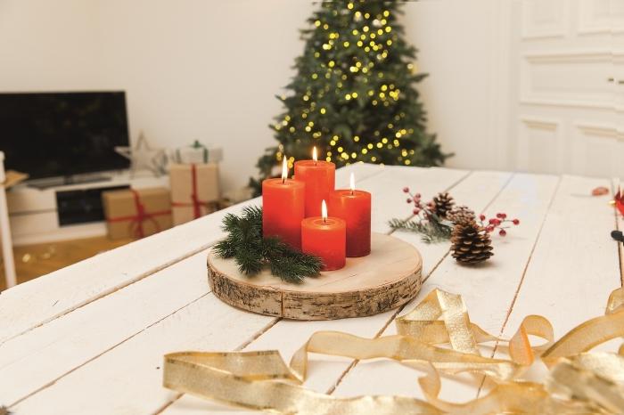 deco de table de noel avec des objets fait maison, diy décoration Noël avec rondelle de bois décorée de bougies et branche sapin