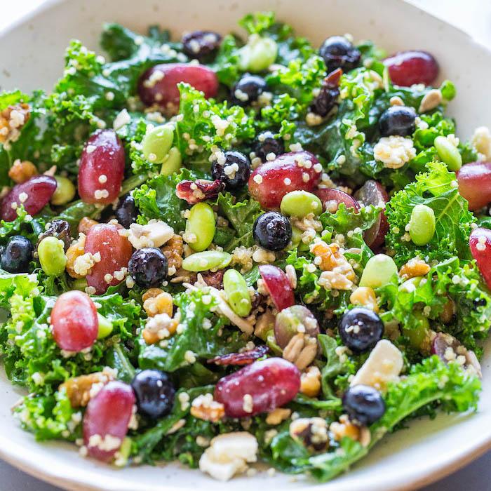 idée de salade chou frisé aux bleuets, haricots verts, quinoa, graines et des raisins frais dans une assiette