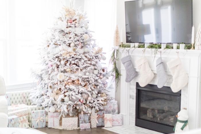 décoration cocooning dans un salon blanc pour Noël avec un gros arbre de Noël décoré en blanc et métalliques