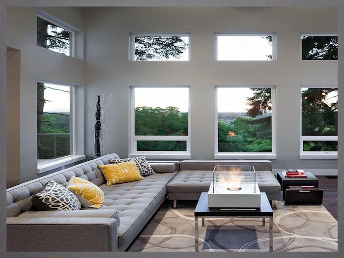 Canapé en angle avec coussins jaunes, association de couleur avec le gris, chambre grise, grandes fenetres