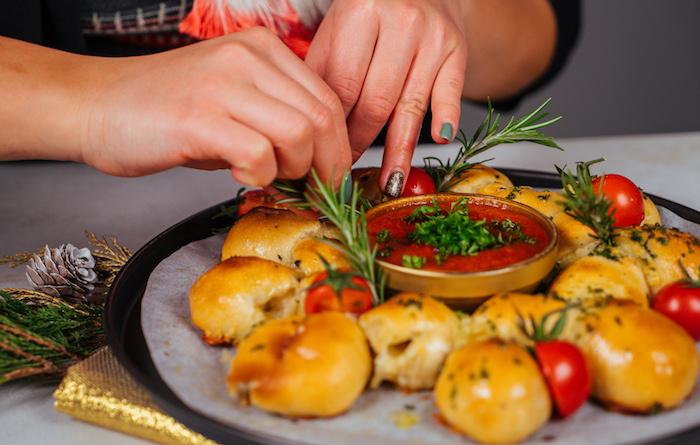 decorer de brins de romarin frais et de tomates cerise divisées en deux, apero dinatoire pour 20 personnes
