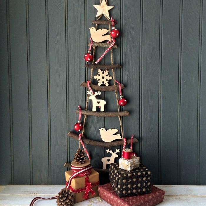 diy sapin suspendu en mini branches de bois foncé avec étoile en bois au sommet et décoration minimaliste avec figurines bois