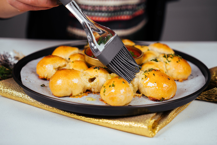pain de boules de pâte à pizza à la mozzarella avec du coriandre frais et beurre en top à servir avec salsa au centre