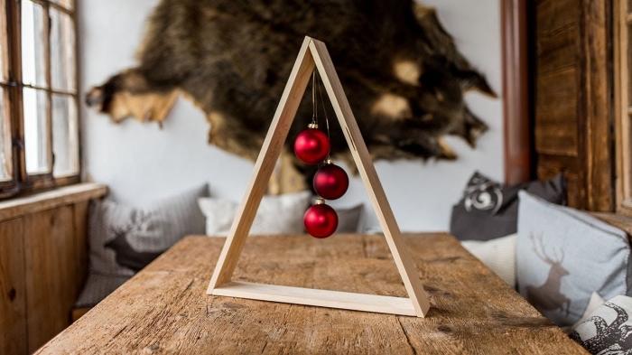 idée deco noel a fabriquer avec peu de matériaux, diy sapin de noel en bois de style scandinave avec ornements de Noël rouges