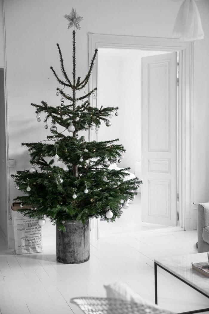 design intérieur tendance minimaliste dans un salon total blanc avec accents en béton et noir, sapin décoré avec boules argentées