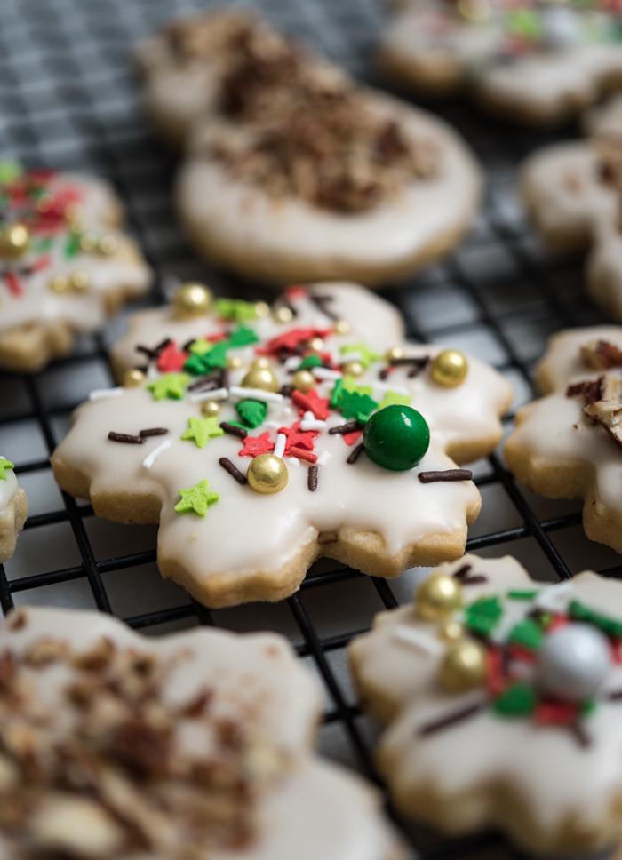 biscuit de noel recette simple de sablé en forme de flocon de neige avec deco vermicelles de sucre, etoiles et perles comestibles, glaçage royal blanc au café
