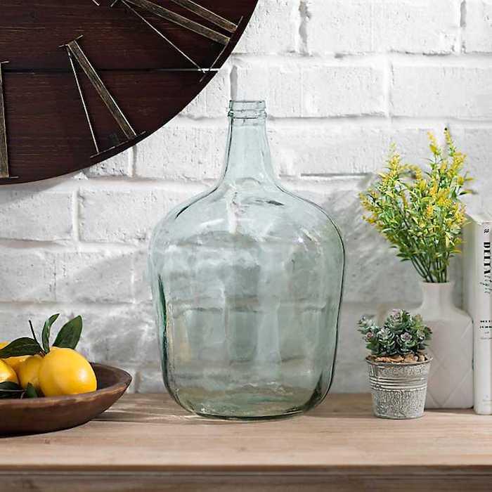 Mur en brique blanche, géante montre sur le mur, citrons pour un peu de jaune, deco dame jeanne, composition pour grosse boteille en verre