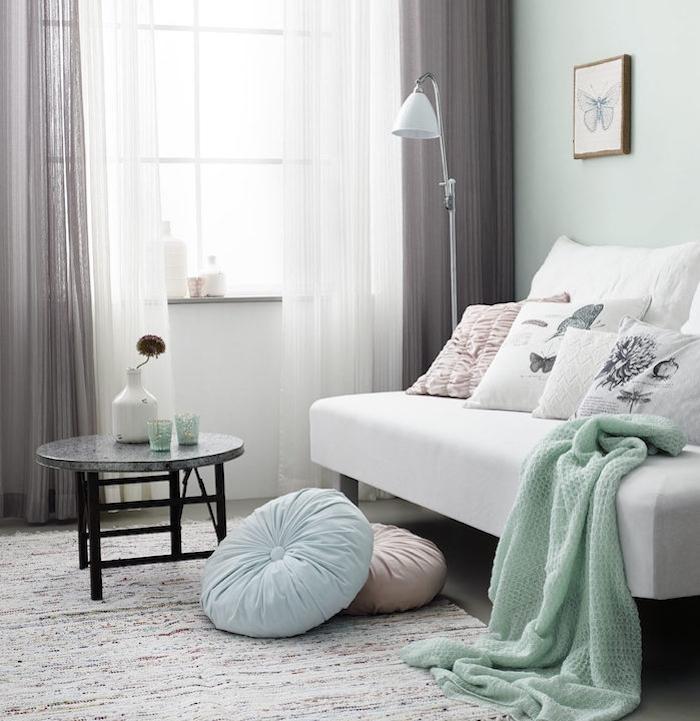 Canapé blanc avec couverture gris menthe, rideaux gris et blanc, dessin de papillon en crayon encadré, deco chambre moderne, idée déco chambre adulte