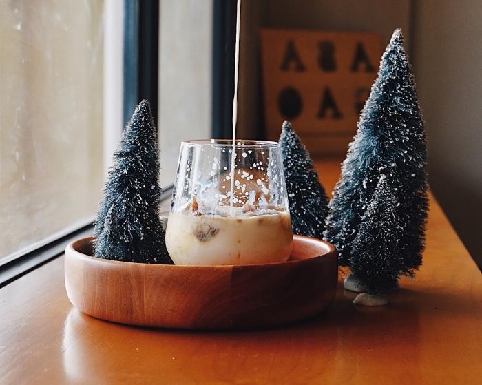 cozy ambiance de Noël avec une boisson au lait et figurines de mini arbres de Noël artificiels, fond d'écran PC pour Noël