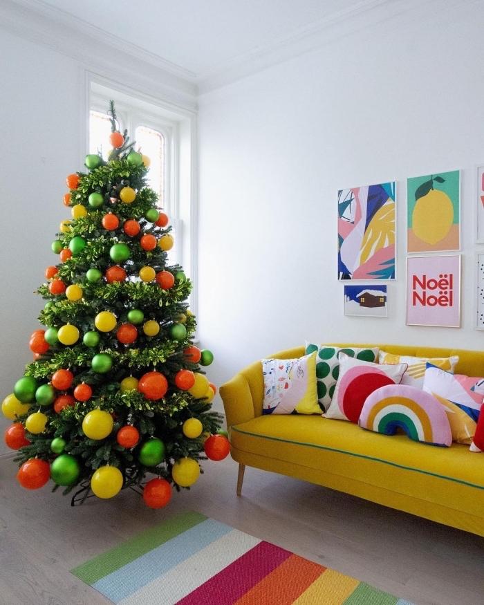 tendance décoration intérieur avec couleurs vert et orange, meubles intérieur de couleur vive jaune, sapin de noel original avec boules orange et jaune