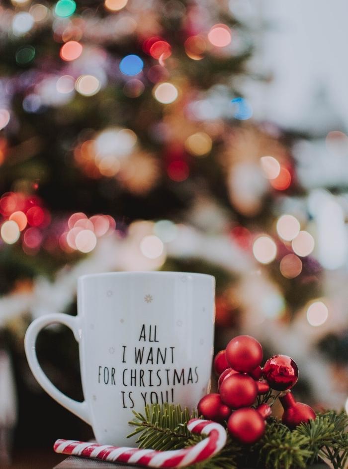 modèle de sapin rouge et blanc avec guirlande lumineuse, wallpaper Noël cocooning avec une tasse joyeux noel