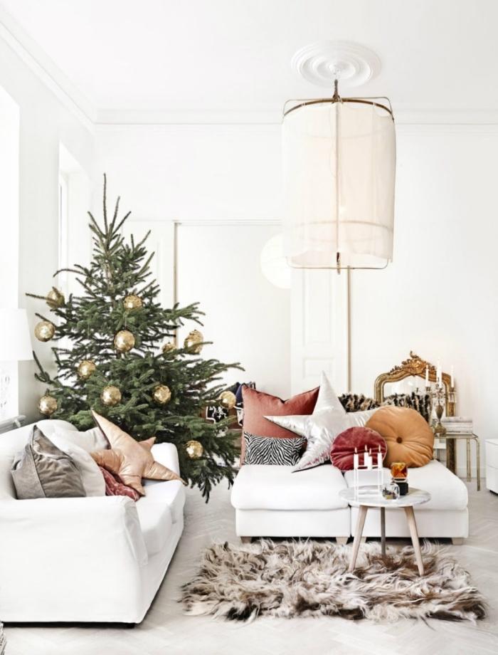 image sapin de noel naturel décoré avec boules en or dans une pièce blanche aménagée avec meubles en blanc