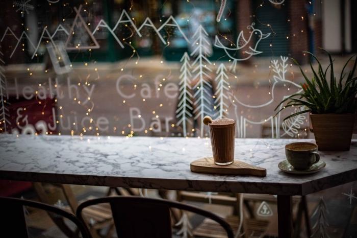 image joyeux noel pour fond d'écran ordinateur, photo cocooning avec boisson chocolat chaude devant vitrine décoré pour Noël