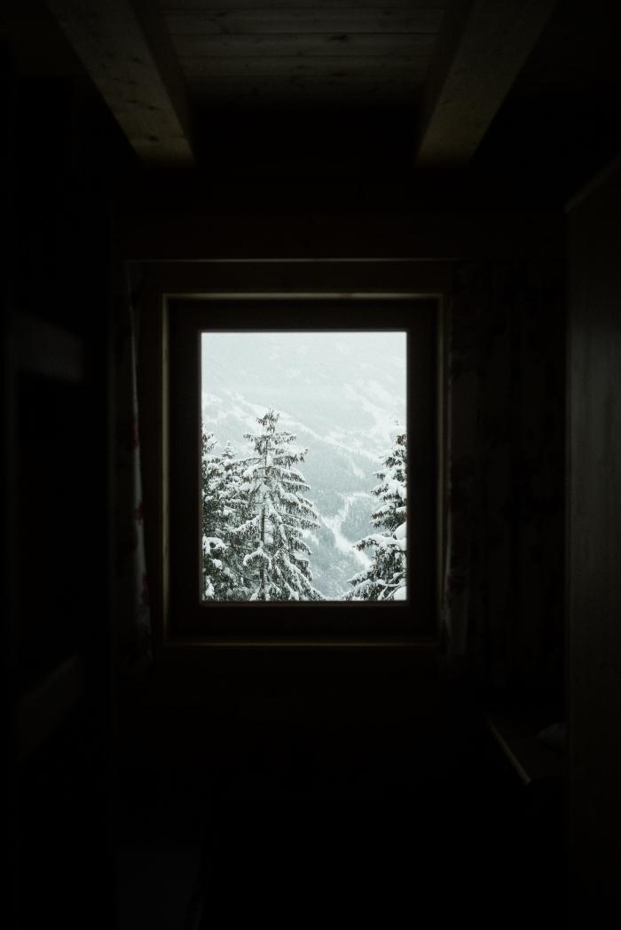 idée belle image de noel pour fond d'écran iphone, photo de paysage enneigé avec sapins devant une fenêtre de chambre sous combles